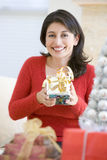 Woman Excited To Open Christmas Present Stock Photography