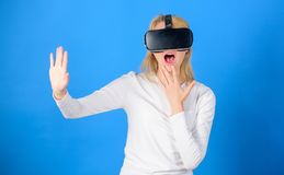 Woman excited using 3d goggles. Woman wearing virtual reality goggles in blue background. Woman using virtual reality. Headset. Futuristic concept stock image