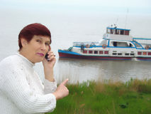 Woman and excursion ship. Ironical look. A business woman with a telephone invites to make a voyage on a river excursion ship Royalty Free Stock Photo