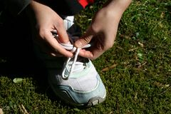 Woman exercise. A woman tying up her shoes, ready for exercise Stock Photo
