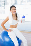Woman on exercise ball with water bottle in fitness studio Royalty Free Stock Images