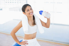 Woman on exercise ball with water bottle in fitness studio Stock Image