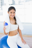 Woman on exercise ball with water bottle in fitness studio Royalty Free Stock Photos