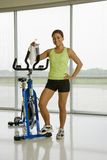 Woman with exercise bicycle. Stock Image