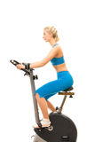 Woman on exercise bicycle Stock Photography