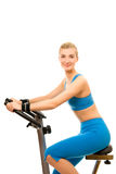Woman on exercise bicycle Stock Images