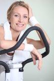 Woman on exercise bike Stock Photos