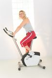 Woman on exercise bike Stock Photos