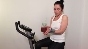 Woman on exercise bike drink smoothie and check blood pressure stock video footage
