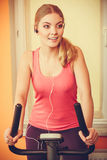 Woman on exercise bike listening music. Fitness Royalty Free Stock Photo