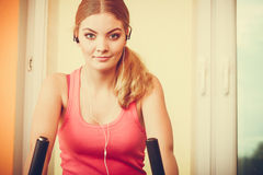 Woman on exercise bike listening music. Fitness Royalty Free Stock Image