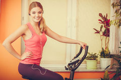 Woman on exercise bike listening music. Fitness Royalty Free Stock Photos