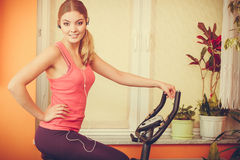 Woman on exercise bike listening music. Fitness Royalty Free Stock Images