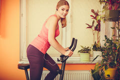 Woman on exercise bike listening music. Fitness Stock Photo