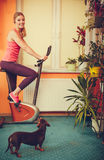 Woman on exercise bike listening music. Fitness Stock Photography