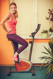 Woman on exercise bike listening music. Fitness Stock Photo
