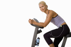 Woman on exercise bike listening to music on earphones, cut out Stock Image