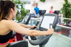 Woman on an exercise bike looking at the tv screen. At the gym Royalty Free Stock Photos