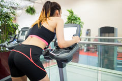 Woman on an exercise bike looking at the tv screen Royalty Free Stock Images