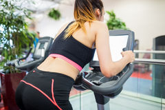 Woman on an exercise bike looking at the tv screen Stock Image