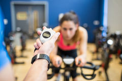 Woman on exercise bike with trainer timing her. At the gym Stock Photos