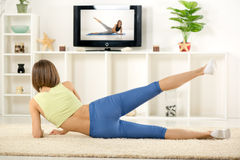 Woman Exercise In Front Of TV Stock Photo