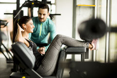 Woman exercise in a gym with the help of her personal trainer Stock Photos