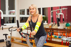 Woman exercise in the gym. Senior, good looking woman exercise in fitness center Royalty Free Stock Images