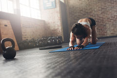 Woman on exercise mat doing stretches at gym Royalty Free Stock Photography