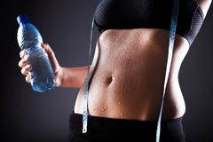 Woman after exercise with measuring tape and water bottle Stock Images