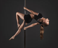 woman exercise pole dance on gray background Royalty Free Stock Photos