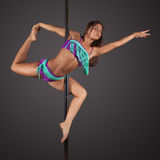 Woman exercise pole dance on gray background Royalty Free Stock Image