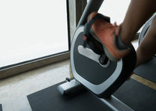 Woman exercise riding bicycle in fitness center Royalty Free Stock Photography
