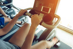 Woman exercise riding bicycle in fitness center Stock Image