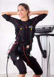 Woman exercise trunk-bending forward  on  electro stimulation ma Royalty Free Stock Photo
