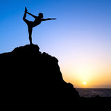 Woman exercise yoga silhouette. Young woman doing beautiful yoga pose king of the dancer, sunset silhouette in mountains over blue sky and clouds with sun Royalty Free Stock Photography