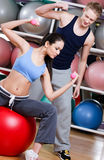 Woman exercises in fitness gym with couch Royalty Free Stock Image