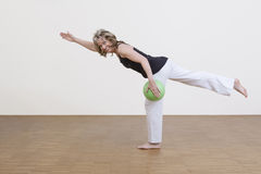 Woman exercises with green ball Royalty Free Stock Image