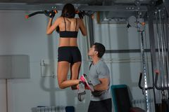 Woman exercises on horizontal bar with instructor Stock Photography