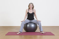 Woman exercises with pilates ball. Female coach shows exercise using a pilates ball Royalty Free Stock Image