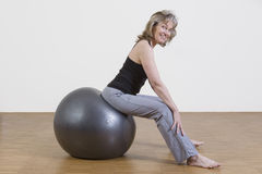 Woman exercises with pilates ball. Female coach shows exercise using a pilates ball Royalty Free Stock Images