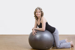 Woman exercises with pilates ball. Female coach shows exercise using a pilates ball Stock Image