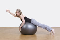 Woman exercises with pilates ball. Female coach shows exercise using a pilates ball Royalty Free Stock Photo