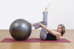 Woman exercises with pilates ball. Female coach shows exercise using a pilates ball Stock Photo