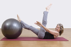 Woman exercises with pilates ball. Female coach shows exercise using a pilates ball Royalty Free Stock Photos