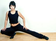 Woman exercising. Beautiful young young woman exercising on wooden floor Royalty Free Stock Photos