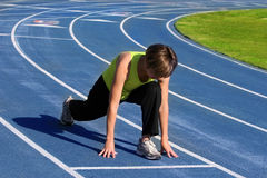 Woman exercising. On a blue racetrack Stock Photography