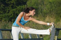 Woman exercising. Young healthy woman exercising outdoor Stock Photography