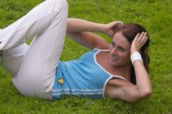 Woman exercising. Young healthy woman exercising outdoor Stock Photos