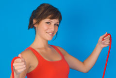 Woman exercising. A young woman exercising with a red tension band Royalty Free Stock Images